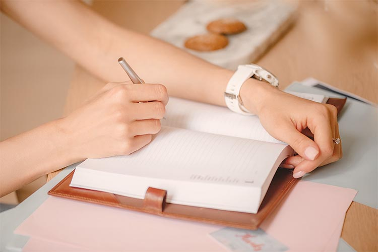 business woman writing in journal